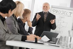 Senior businessman presenting on meeting. To mid-adult coworkers, smiling, gesturing with both hands royalty free stock photos