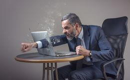 Enough with this stupid technology. Senior businessman punching a hole through his laptop screen, furious and enraged stock photos