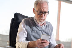 Senior businessman reading a message on his mobile phone, hard light Stock Photography