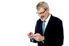 Senior businessman reading a text message. Smiling business executive texting on his cell phone Royalty Free Stock Photos
