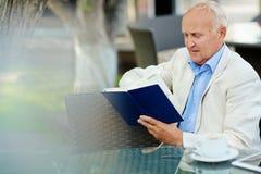 Senior Businessman Resting in Cafe Stock Images