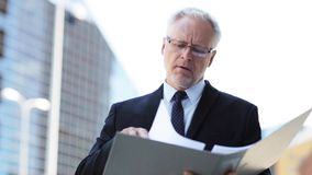 Senior businessman with ring binder folder in city. Business, office work and people and concept - senior businessman paging documents in ring binder folder on stock footage