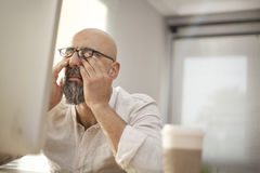 Senior businessman rubbing his tired eyes. On office royalty free stock image