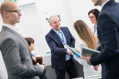 Senior Businessman Shaking Hands With Female Colleague. In lecture hall stock photography