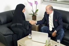 Senior Businessman Shaking hands with Woman wearing hijab Royalty Free Stock Photo