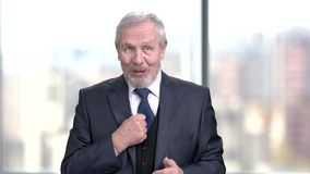 Senior businessman sharing with experience. Friendly speaking company leader on blurred background stock video