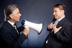 Senior Businessman Shouting At His Employee. Studio shot of a senior businessman shouting at his employee Stock Photo