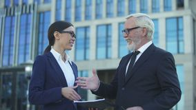 Senior businessman signing contract with young female consultant, handshake stock footage