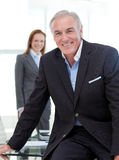 Senior businessman sitting on a conference table Stock Photo