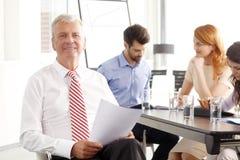 Senior businessman sitting at meeting Stock Photos