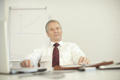 Senior businessman sitting relax at his desk. Smiling royalty free stock image