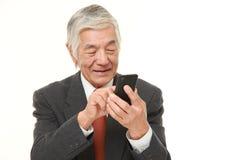 Senior businessman with a smart phone. Studio shot of senior Japanese businessman on white background Stock Images