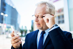 Senior businessman with smartphone in city Stock Photos