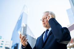 Senior businessman with smartphone in city Royalty Free Stock Photos