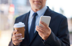 Senior businessman with smartphone and coffee Stock Photography