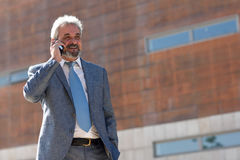 Senior businessman with smartphone outside of modern office buil Royalty Free Stock Photos