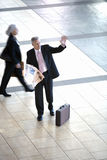 Senior businessman standing in airport, holding financial newspaper, waving, elevated view Royalty Free Stock Images