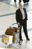 Senior businessman standing with luggage trolley in airport, smiling, elevated view Royalty Free Stock Photos