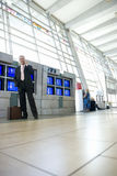 Senior businessman standing beside row of flight information screens in airport, using mobile phone, smiling, portrait (surface le Royalty Free Stock Photos