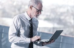 Senior businessman standing and working on his laptop royalty free stock photos