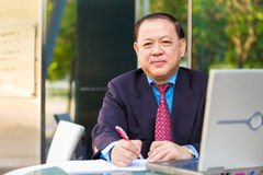 Senior businessman in suit writing proposal. Portrait Stock Photo