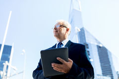 Senior businessman with tablet pc on city street Royalty Free Stock Photos
