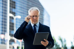 Senior businessman with tablet pc on city street Stock Images