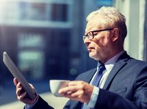 Senior businessman with tablet pc drinking coffee stock images