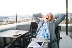 Senior businessman with a tablet in rooftop cafe Stock Photos