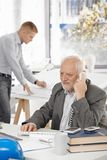Senior businessman talking on landline phone. Sitting at office desk, young colleague working in background Royalty Free Stock Photo