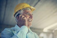 Senior architect using smart phone. Senior businessman talking on mobile phone Royalty Free Stock Images