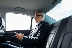 Senior businessman texting on smartphone in car. Transport, business trip, technology and people concept - senior businessman texting on smartphone and driving Stock Images