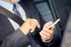 Senior businessman texting on smartphone in car Stock Photos