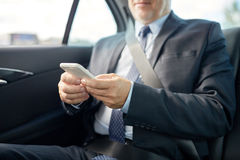 Senior businessman texting on smartphone in car Royalty Free Stock Photography