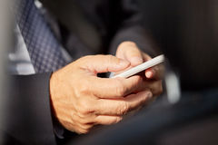 Senior businessman texting on smartphone in car Royalty Free Stock Images