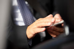 Senior businessman texting on smartphone in car Royalty Free Stock Photos