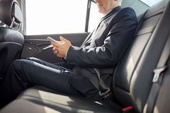Senior businessman texting on smartphone in car Stock Photo