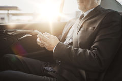 Senior businessman texting on smartphone in car Stock Photography