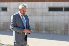 Senior businessman texting with smartphone outside of modern off. Portrait of a senior businessman texting with a smart phone outside of modern office building Royalty Free Stock Photos