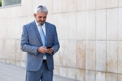 Senior businessman texting with smartphone outside of modern off. Portrait of a senior businessman texting with a smart phone outside of modern office building Stock Photos