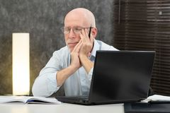 Senior businessman is tired in the office stock image
