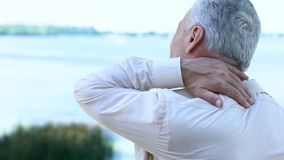 Senior businessman touching aching neck, sedentary lifestyle consequences. Stock photo stock photos