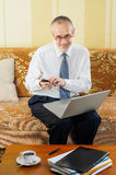 Senior Businessman Typing an Sms Stock Images