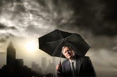 Senior businessman under the rain Stock Photo