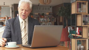 Senior businessman uses laptop at the cafe. Senior caucasian businessman using laptop at the cafe. Attractive aged man dressed in suit looking at the computer stock footage