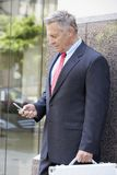 Senior Businessman Using Cellphone. While standing against wall Royalty Free Stock Images