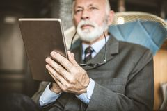 Senior businessman using digital tablet. Focus on hand. royalty free stock image