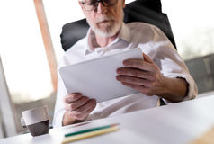 Senior businessman using a digital tablet, hard light. Senior businessman using a digital tablet in office, hard light Royalty Free Stock Images