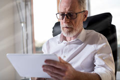 Senior businessman using a digital tablet, hard light. Senior businessman using a digital tablet in office, hard light Stock Photo