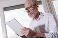 Senior businessman using a digital tablet, hard light. Senior businessman using a digital tablet in office, hard light Stock Photos